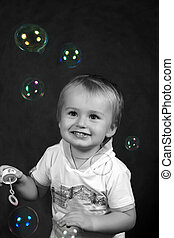 Soap bubbles - The small boy with soap bubbles in studio