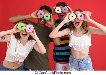 Young cheerful group of friends friends standing with donuts...