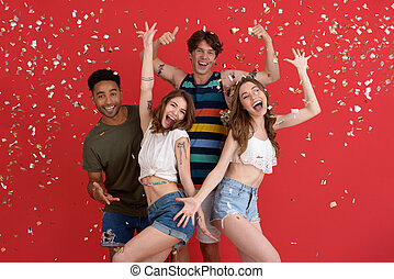 Cheerful group of friends standing isolated over confetti -...
