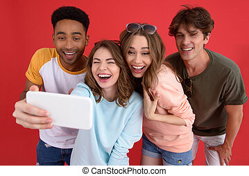 Cheerful group of friends make selfie by phone. - Image of...