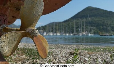 Rusty Propeller near Shore - Close-up shot of a fishing boat...