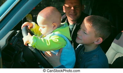 father and two sons in the car