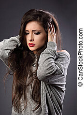 Stressed unhappy casual woman with headache in grey sweater...
