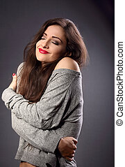 Happy makeup woman with red lipstick hugging herself with...