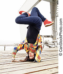 Breakdancer doing a handstand - Young female breakdancing in...
