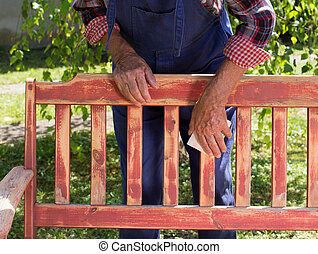 Old man sandblasting bench in garden - Close up of senior...