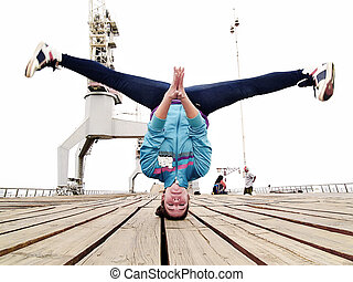 Breakdancer handstanding with head - Young female...