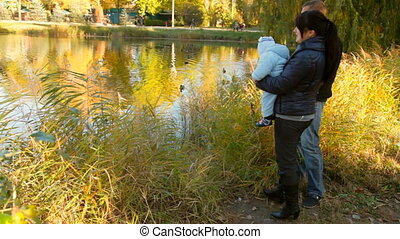 family near a pond - family in a park near a pond with ducks...