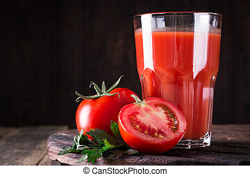 Glass of tomato juice with vegetables on wooden background