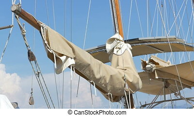 Old Sail Rolled on Mast - Vintage yacht sail rolled on the...