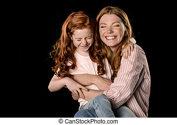 Beautiful redhead mother and daughter having fun together isolated on black