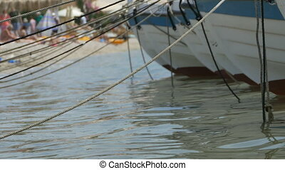 Boats Moored near Beach - Boats moored with ropes on the...