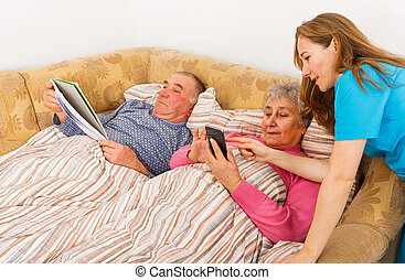 Elderly couple and young caregiver - Senior man reading and...