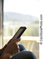 man reading in a tablet or e-reader - closeup of a young...