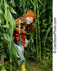 Young female explores a corn maze.