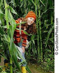 Young female explores a corn maze.