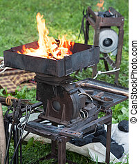 The furnace heats the metal in the fire. Hot coals.The...