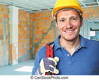 smiling manual worker - happy handyman at work in...