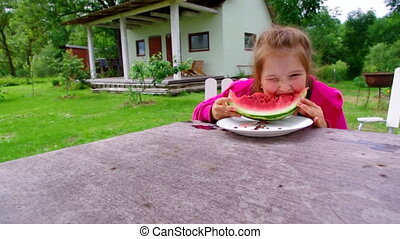 Little girl eating watermelon with in the garden
