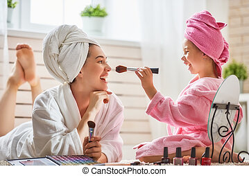 Mother and daughter are doing make up - Happy loving family....