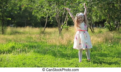 Funny little kid playing outside in beautiful summer meadow
