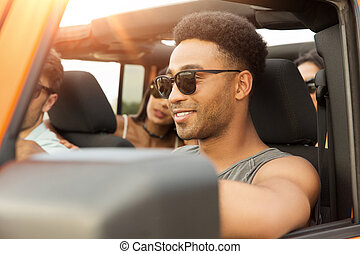 Smiling young african man driving a car and having fun with...