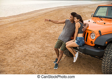 Beautiful young couple embracing while leaning on their car...