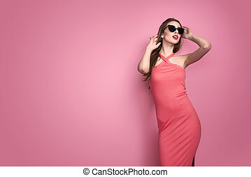 Portrait of young beautiful slim sexy young woman in sexy dress with red sensual lips on pink background in studio