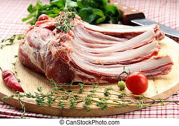 Lamb meat cut into steaks on wooden board