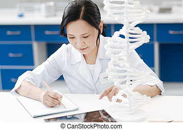 Smart delighted geneticist taking notes - Genetic research....
