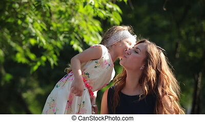 Mother and her little daughter having fun outdoors. Beautiful family-mom and her child girl hugging and kissing in summer park together.