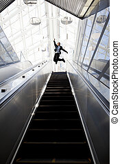 Happy businessman and Escalator in the modern building