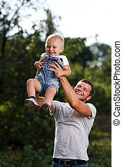 Happy moments. Father throws up his son in the sky at sunset...