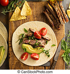 Making tacos with grilled steak, avocado and tomatoes,...