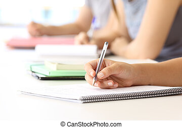 Student hand taking notes in a classroom