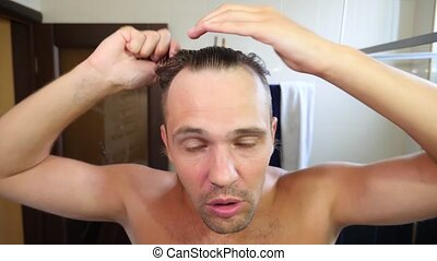 Young attractive man inspects a receding hairline in the...