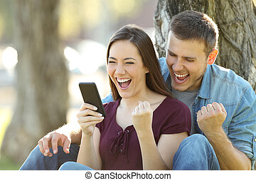 Excited couple reading news in a phone - Excited couple...