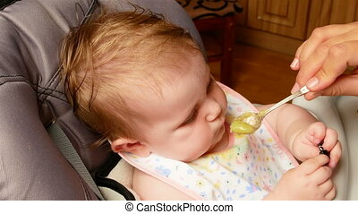 feeding a small child - Mom feeds from spoon her little...