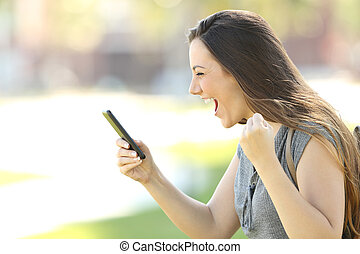 Profile of an excited woman using a phone - Profile of a...