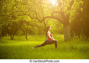 Young woman exercising yoga outdoors.