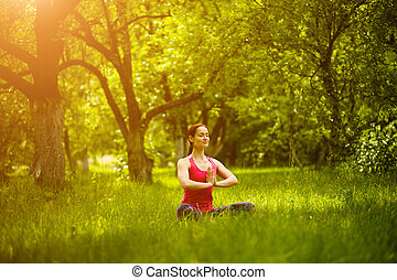 Young female mediating in garden. Woman practicing yoga,...