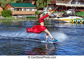 Woman on the lake goes for a wakeboard ride. - Woman enjoys...