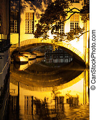 Boat reflection on water canal by night in Bruges, Belgium.