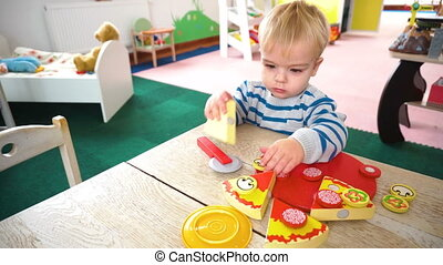 Little boy playing with lots of colorful plastic blocks,...