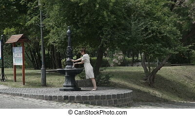 Woman drinking from public water fountain, thirst and summer. cups her hands and gathers water in them