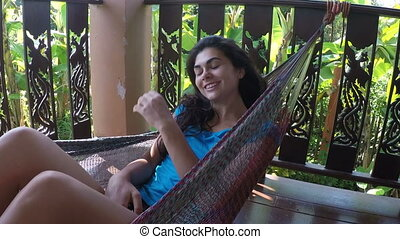 Happy Woman Lying In Hammock Relaxing On Summer Terrace...