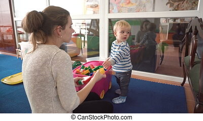 mother playing with her baby boy in room with colourful...