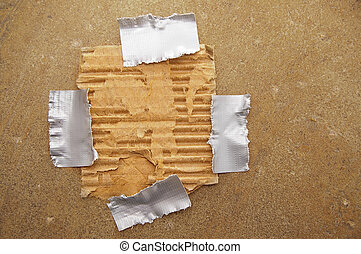 piece of ripped brown paper, taped to grunge background