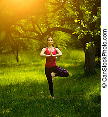 Young woman balancing in tree pose practicing yoga.