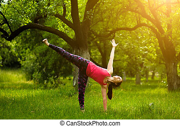 young woman standing in half moon pose, while practicing yoga.